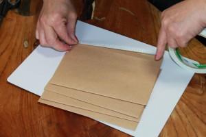 折った用紙の開いている口側に両面テープを貼っていく。裏返して同じように開いている口側に貼っていく